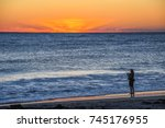 A Fisherman On The Beach As Th...
