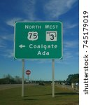 Small photo of ADA, OKLAHOMA—SEPTEMBER 2017: Directional road sign in Ada with arrows pointing to the direction of Coalgate at Highway 75.