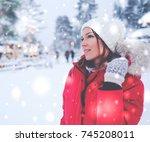 happy woman in a snow landscape   Shutterstock . vector #745208011