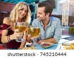 romantic couple making cheers... | Shutterstock . vector #745210444