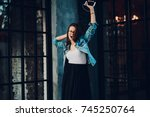 happy young woman dancing while ... | Shutterstock . vector #745250764