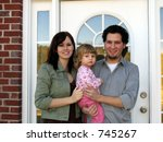 Family at the front door of their new home - stock photo