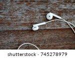 white headphones on old wooden... | Shutterstock . vector #745278979