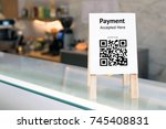 Small photo of Qr code payment , online shopping , cashless society technology concept. Coffee shop accepted digital pay without money , wood stand tag on table.