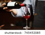 Small photo of Waiter pouring red wine into wineglass. Sommelier pours alcoholic drink