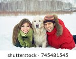 young couple with a dog on a... | Shutterstock . vector #745481545