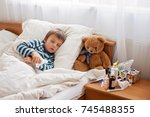 sick child boy lying in bed... | Shutterstock . vector #745488355