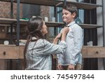 Small photo of Mother helping her little son get dressed and tie a necktie