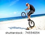 Small photo of A teenager with bike making a trick on a beach