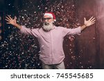 Small photo of Happy modern Santa wants to hug you! Christmas and New year party with Santa in gold confetti. Modern bearded man in Santa's hat and fashion glasses have a fun and want's to hug all of the children.