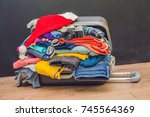 a suitcase with clothes and a... | Shutterstock . vector #745564369