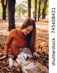 Stock photo beautiful laughing red haired girl playing with her big gray dog in a pile of fallen autumn leaves 745608421