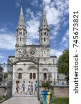 Small photo of France, Saone-et-Loire, Macon: People residents tourists cross square in front of main entrance of famous French Catholic church St. Pierre in the center of the town with blue sky. August 05, 2017
