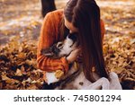 Stock photo young red haired girl in an orange sweater playing with her dog in fallen autumn leaves 745801294