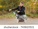 Stock photo woman gives a command to her dog puppy siberian husky in the autumn park dog training 745823521