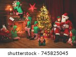 Small photo of Santa Claus and little elves before Christmas in his house by fireplace and Christmas tree