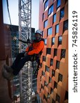 Small photo of Male abseiler orange t-shirt working on high rise building site in Sydney city CBD, Australia