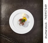 Small photo of Chocolate fondant with ice cream, slice of orange and mint leaves on black background