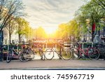 Stock photo bicycle on the bridge with netherlands traditional houses and amsterdam canal in amsterdam 745967719