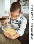 young boy in glasses whisking... | Shutterstock . vector #746051311