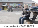 sad boy outside at schoolyard   Shutterstock . vector #746118829