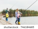 happy family in raincoats and... | Shutterstock . vector #746184685