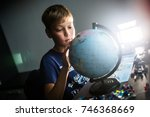 the schoolboy looks at the globe   Shutterstock . vector #746368669