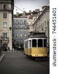 Small photo of A yellow old tram riding along Figueira Square in the city of Lisbon, Portugal