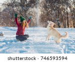 Stock photo happy beautiful young woman blowing snowflakes from her hands to her dog golden retriever in a 746593594