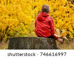 Boy In Red Jacket Sitting On A...