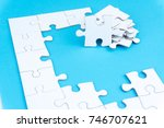 Small photo of half complete white color puzzle on blue background. Task for completion concept. selective focus