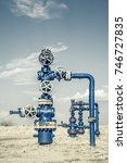 Small photo of Production wellhead with valve armature. Oil, gas industry. Petroleum theme. Toned.