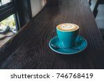 Small photo of the green cup of coffee on wood table in vintage color mood