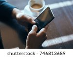 phone in hand close up  cup of... | Shutterstock . vector #746813689