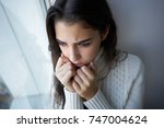 sad woman looks out the window  ... | Shutterstock . vector #747004624