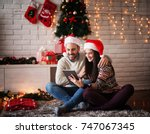 adorable young couple sitting... | Shutterstock . vector #747067345