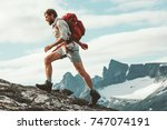 man trail running in mountains... | Shutterstock . vector #747074191