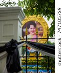 Small photo of September 10, 2017. Wide angle of Queen Sirikit's portrait behind an iron fence and black funeral drapings during a storm. Metropolitan Electricity Authority, Bangkok, Thailand. Travel editorial.