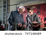 a young apprentice adjusting a... | Shutterstock . vector #747148489