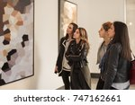 Stock photo four girl friends looking at modern painting in art gallery abstract painting 747162661