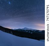 Small photo of Winter landscape of a mountain range at night. Stars over the mountain range. Mountain slopes covered with snow.