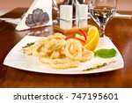 fried calamari rings with lemon | Shutterstock . vector #747195601