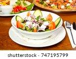 fresh greek salad in a bowl... | Shutterstock . vector #747195799