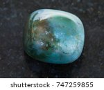 Small photo of macro shooting of natural mineral rock specimen - polished Bloodstone (Heliotrope) gemstone on dark granite background