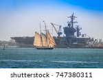 Small photo of San Diego, USA - October 8, 2017: Replica of the Schooner AMERICA passes the American Navy aircraft carrier USS CARL VINSON (CVN-70) near North Island Naval Air Station.