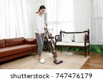 young asian woman with vacuum... | Shutterstock . vector #747476179