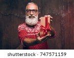 senior bearded man holding gift ... | Shutterstock . vector #747571159