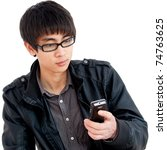 A young Chinese man looking at cell phone - stock photo