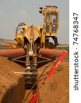 Trencher machine in sandy ditch on pipeline construction site - stock photo