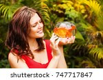 woman looking at a gold fish in ... | Shutterstock . vector #747717847